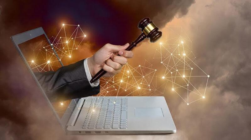 Mano con martello da giudice che esce da un computer portatile